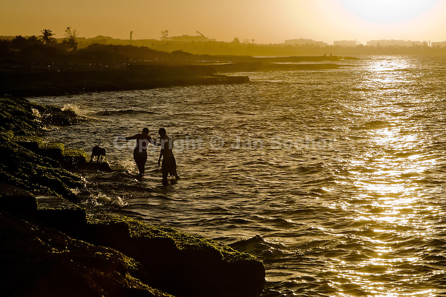 """Cuban lovers are seen bathing with their dog in the sea during the sunset in Alamar, a huge public housing complex in the Eastern Havana, Cuba, 12 February 2009. The Cuban economic transformation (after the revolution in 1959) has changed the housing status in Cuba from a consumer commodity into a social right. In 1970s, to overcome the serious housing shortage, the Cuban state took over the Soviet Union concept of social housing. Using prefabricated panel factories, donated to Cuba by Soviets, huge public housing complexes have risen in the outskirts of Cuban towns. Although these mass housing settlements provided habitation to many families, they often lack infrastructure, culture, shops, services and well-maintained public spaces. Many local residents have no feeling of belonging and inspite of living on a tropical island, they claim to be """"living in Siberia""""."""
