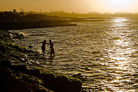 "Cuban lovers are seen bathing with their dog in the sea during the sunset in Alamar, a huge public housing complex in the Eastern Havana, Cuba, 12 February 2009. The Cuban economic transformation (after the revolution in 1959) has changed the housing status in Cuba from a consumer commodity into a social right. In 1970s, to overcome the serious housing shortage, the Cuban state took over the Soviet Union concept of social housing. Using prefabricated panel factories, donated to Cuba by Soviets, huge public housing complexes have risen in the outskirts of Cuban towns. Although these mass housing settlements provided habitation to many families, they often lack infrastructure, culture, shops, services and well-maintained public spaces. Many local residents have no feeling of belonging and inspite of living on a tropical island, they claim to be ""living in Siberia""."