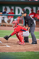 Jeans Flores (13) of the Orem Owlz on defense against the Ogden Raptors as home plate umpire Rene Gallagos handles the calls at Lindquist Field on June 20, 2019 in Ogden, Utah. The Owlz defeated the Raptors 11-8. (Stephen Smith/Four Seam Images)