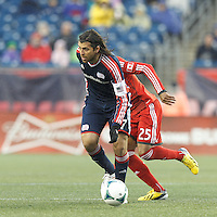 New England Revolution midfielder Juan Carlos Toja (7) under pressure passes the ball.  In a Major League Soccer (MLS) match, the New England Revolution (blue) defeated Toronto FC (red), 2-0, at Gillette Stadium on May 25, 2013.
