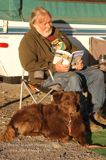 Man relaxing with his dog, while reading a Death Valley Guide Book, Stovepipe Wells, Death Valley National Park, California