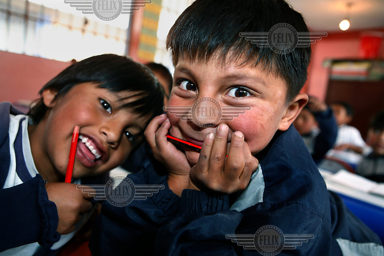 Children pose for the camera in a class at a primary school in the area of Quito.