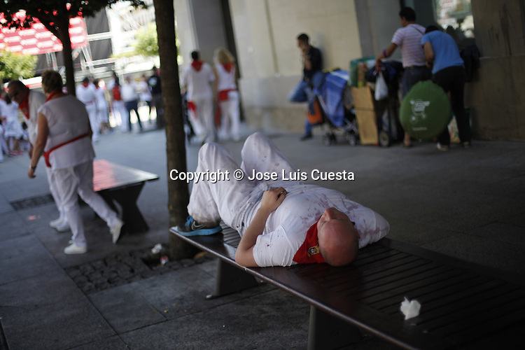 Reveler is sleeping at the street after the night party, in Pamplona, Spain. San Fermin festival is worldwide known because the daily running bulls.