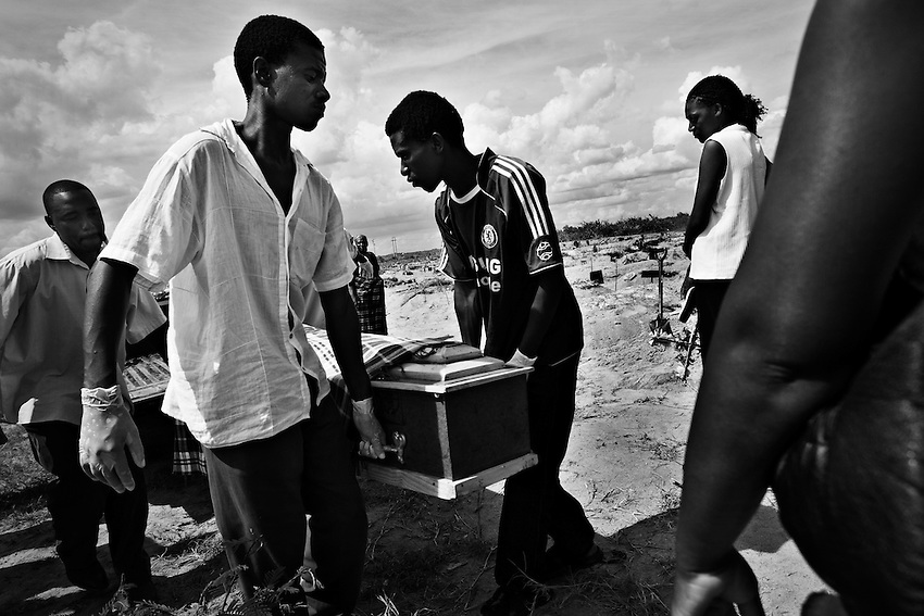 Pallbearers carry the body of Emmely Munyonga, 74, who died of cholera and is being buried in the B wing of Granaville Cemetary, which has been designated for cholera victims, near Budiriro, Zimbabwe, Sunday, December 14, 2008.