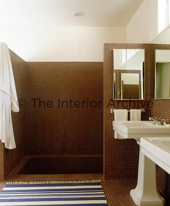 Brown mosaic tiling, large pedestal basins and a sunken bath create an air of masculine luxury in this bathroom