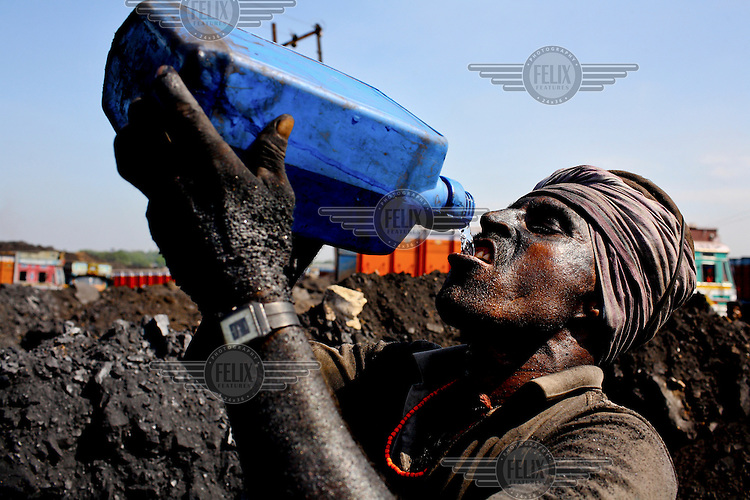 A contract labourer, at an open cast coal mine, drinks from a plastic container of water. He spends 10 - 12 hours a day carrying baskets of rock coal for which he'll earn less than GBP 2.20. /Felix Features