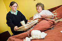 Young carers looking after elderly relatives.  Photo posed by models.  Model released...Young girl in school uniform brings a tray of tea and biscuits to her bed bound grandmother / elderly / disabled relative...Following info from http://www.barnardos.org.uk :  .With so many adult responsibilities, young carers often miss out on opportunities that other children have to play and learn. Many struggle educationally and are often bullied for being 'odd'. They can become isolated, with no relief from the pressures at home, and no chance to enjoy a normal childhood. They are afraid to ask for help as they fear letting the family down or being taken into care..Facts and figures.othe average age of a young carer is 12..othe 2001 census shows that there are 175,000 young carers in the UK, 13,000 of whom care for more than 50 hours a week..omore than half of young carers live in one-parent families and almost a third care for someone with mental health problems.