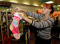 NWA Media/FLIP PUTTHOFF <br /> STOCKINGS TO STUFF<br /> Ann Cook of Fayetteville arranges her hand-made Christmas stockings on Friday Dec. 5 2014 at the Frisco Station Mall holiday crafts fair in Rogers. Cook's stockings include sports teams and decorative themes and are among several Christmas items she makes. The fair continues today at the mall.