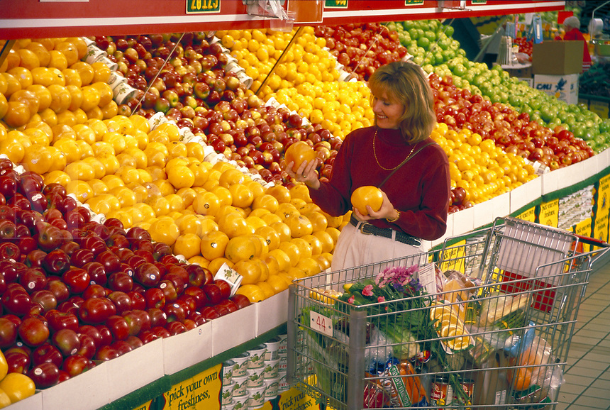 adult woman shops in the fruit section of a supermarket.