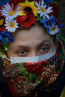 A peaceful demonstrator wears flowers costume  in Maidan square. Kiev, Ukraine
