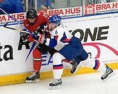 Michal Korenko (Lewiston Maineiacs - Slovakia) checks Gregory Sciaroni (HC Ambri-Piotta - Switzerland) along the boards. The Suisse defeated Slovakia 2-1 in a 2007 World Juniors match on January 2, 2007, at FM Mattson Arena in Mora, Sweden.