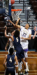 SIOUX FALLS, SD - MARCH 10:   Aziz Leeks #22 from the College of Idaho tips the ball to the basket over Reginald Kissoonlal #5 from Marian during their quarterfinal game at the 2018 NAIA DII Men's Basketball Championship at the Sanford Pentagon in Sioux Falls. (Photo by Dave Eggen/Inertia)