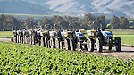 Lineup of blue New Holland tractors in a lettuce field in the Salinas Valley, Santa Lucia Range, California.