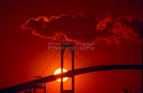 Sunset behind pilings of Newport Bridge in Newport Ri.