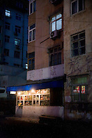 Lights illuminate a small neighborhood kiosk store in an apartment complex in Qingdao, Shandong, China.