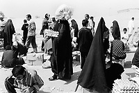 "Iraq. Baghdad. Al Sadr City. The women wear the ""abaya"" (body-covering black garments) and the ""hidjab"" (islamic headscarf) on their heads to cover the hair. Women shop in the open air market . © 2003 Didier Ruef"