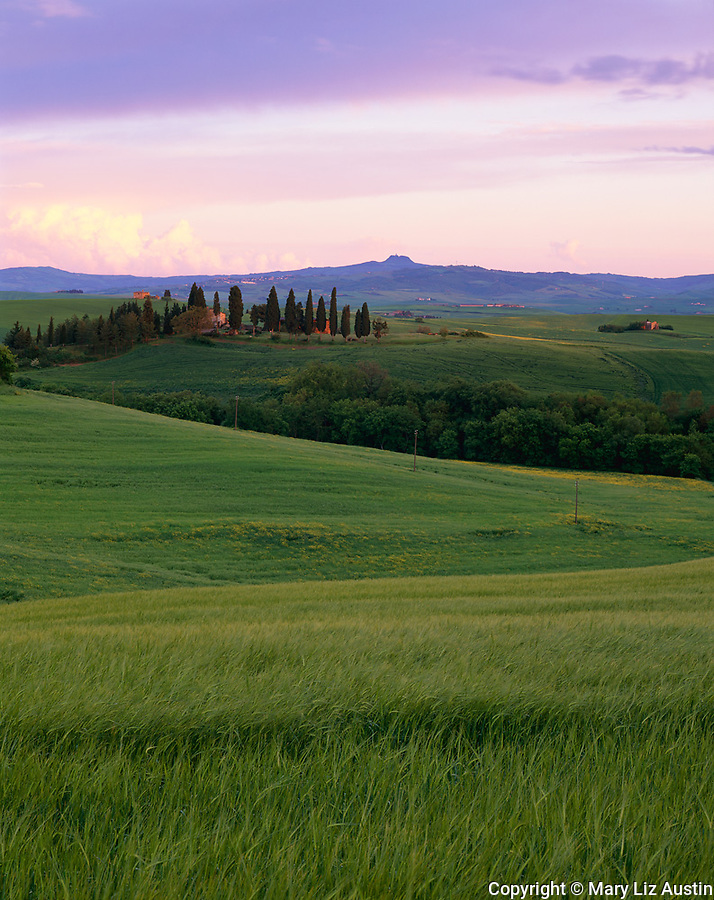 Tuscany, Italy<br /> Sunset colors the clouds of a clearing storm over the rolling hills and farmlands near Pienza in the Val d'Orcia