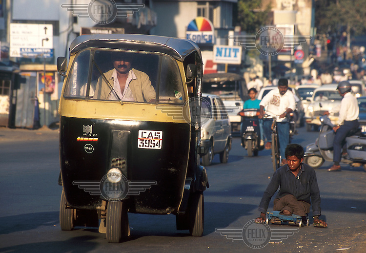 India, Karnataka, Bangalore..Crippled youth on a trolley in traffic downtown...Mark Henley