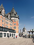 People walking on the Dufferin terrace boardwalk by the Fairmont Le Château Frontenac castle on a sunny day, luxury grand hotel Chateau Frontenac, National Historic Site of Canada. Old Quebec City, Quebec, Canada. Terrasse Dufferin, Ville de Québec.. Spring 2017.
