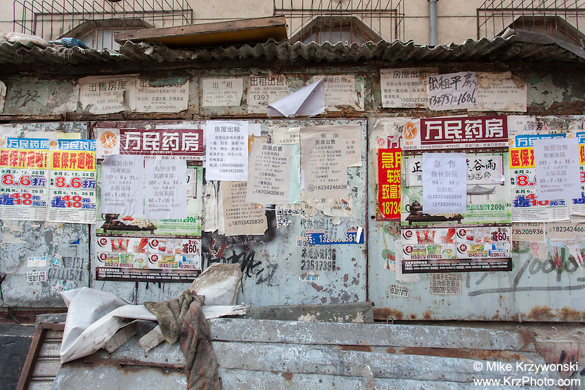 A wall cluttered w/ posted ads in Datong, China
