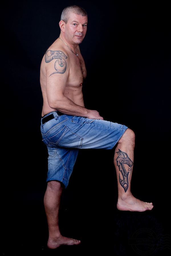 "Danish man with at viking style double headed dragon tattooed across his shoulders. On lower right leg he has a ""dog-dragon"" to remember the dogs he had. For each dog there is a star tattooed on the dragons neck. The dragons is tattooed by Erik Reime from Kunsten på Kroppen."