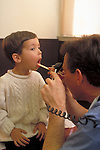 doctor examining young boy's throat