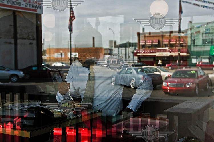 """At the Cadillac General Motors (GM) dealership """"Dalgleish"""", employee Mike Spencer is having a cheap lunch. Car dealerships in Detroit, Michigan have been seriously affected by the drop in car sales over the last few years."""