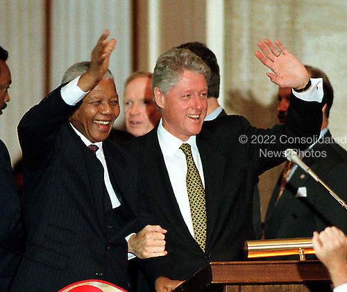 Washington, DC - September 23, 1998 -- President Nelson Mandela of South Africa and United States President Bill Clinton wave to the audience after the former's acceptance of the Congressional Gold Medal in The United States Capitol Rotunda on Wednesday, September 23, 1998...Credit: Ron Sachs / CNP