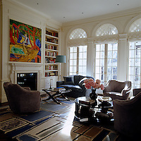 Light streams in through the three pairs of French windows onto the boldly patterned rug in the living room furnished with suede upholstered club chairs