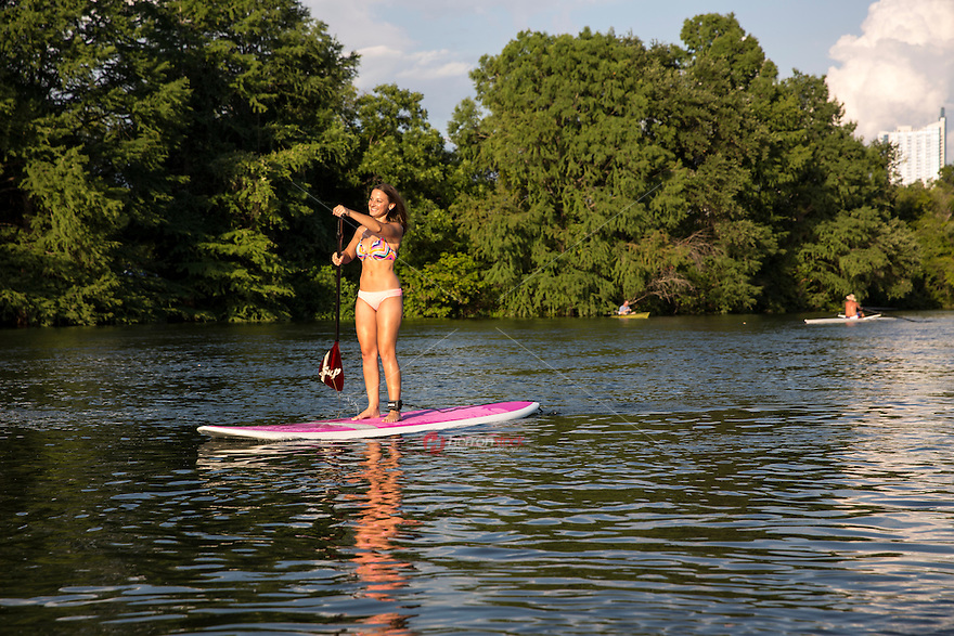 A young attractive fit woman in a bikini on a paddle board exercising on Lady Bird Lake, Austin, Texas