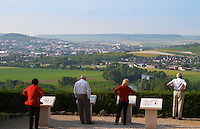 Four people in red white and black standing at a view spot overlooking the Vallee de la Marne, the river and the vineyards with Epernay in the distance (each one with the hand on the hips), the village of Hautvillers in Vallee de la Marne, Champagne, Marne, Ardennes, France