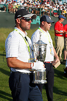 A USGA official holds the trophy on the 18th hole waiting for the winner to be determined during the 118th U.S. Open Championship at Shinnecock Hills Golf Club in Southampton, NY, USA. 17th June 2018.<br /> Picture: Golffile | Brian Spurlock<br /> <br /> <br /> All photo usage must carry mandatory copyright credit (&copy; Golffile | Brian Spurlock)