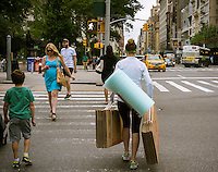 A woman carries moving supplies in the Flatiron neighborhood of New York on Saturday, June 20, 2015.  (© Richard B. Levine)