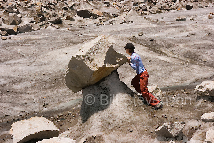 A woman pushing a rock on a glacier