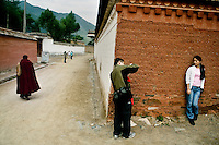 Tourists pose for pictures while Tibetan Buddhist monks walk by at the Labrang Monastery in Xiahe, Gansu, China. Xiahe, home of the Labrang Monastery, is an important site for Tibetan Buddhists.  The population of the town is divided between ethnic Tibetans, Muslims, and Han Chinese.