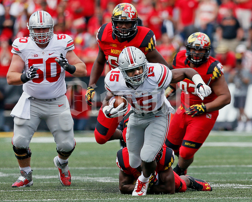 Ohio State Buckeyes running back Ezekiel Elliott (15) gains yards followed by Maryland Terrapins defensive lineman Andre Monroe (93) and Maryland Terrapins linebacker L.A. Goree (53) in the third quarter of their game at Byrd Stadium in College Park, Maryland on October 4, 2014. (Columbus Dispatch photo by Brooke LaValley)