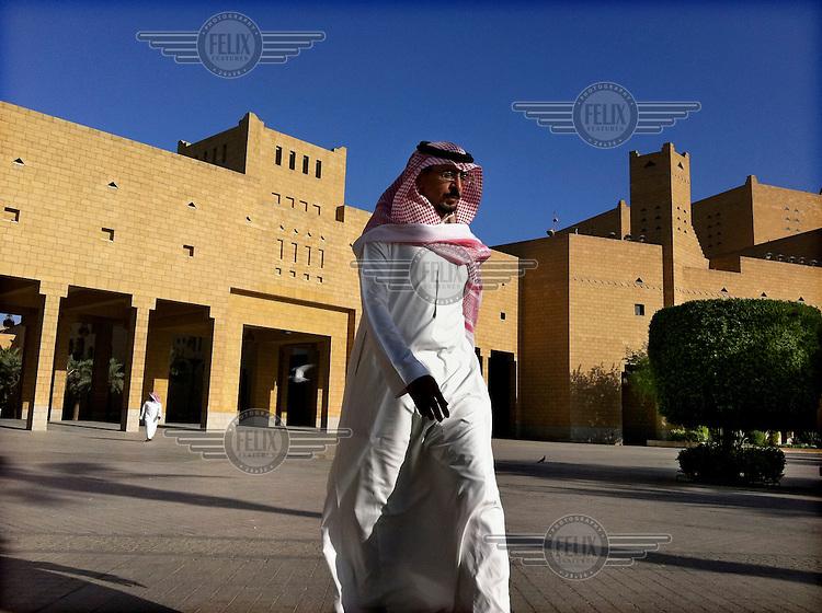 A man walking on Al Safa Square in Ad Dirah.