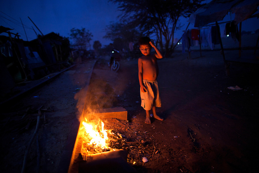 A boy looks at a make-shift fire along the railway tracks that skirt the edge of Boeung Kak lake in Phnom Penh, Feb 4, 2011.