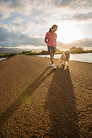 Woman walking with dog on bridge at sunset, North Shore, O'ahu