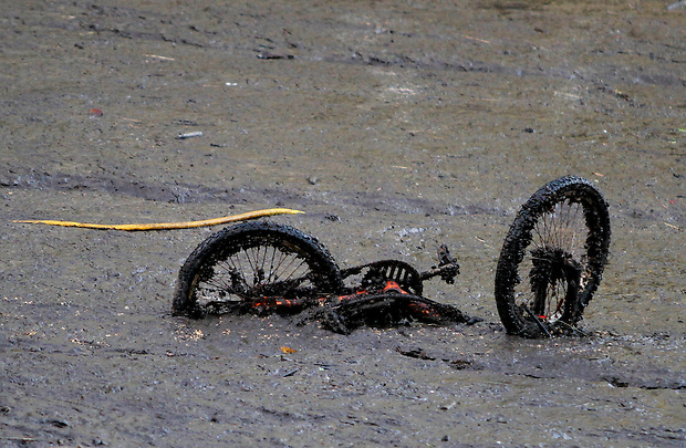 A bicycle is revealed in the floor of Lake Delhi Sunday morning, July 25, 2010 as water empties from the lake.  Flood water breached and destroyed the dam the day before, emptying the nine mile long lake.