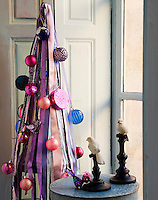 An alternative Christmas tree made of a chicken-wire structure covered with colourful ribbons and decorated with large vibrant baubles