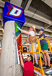 "Naomi Maturino, below, Brother Mark Elder, C.M., and Emily Spurgeon '16, install a mural around a large concrete column, Saturday, July 28, 2018, under the Fullerton ""L"" Station in Lincoln Park. The mural features a montage of historical images highlighting the 50th anniversary of DePaul's Black Student Union. Other murals installed at the site included a caricature of DePaul basketball star George Mikan, and a mural celebrating the opening of the university's Loop Campus.<br /> <br /> Elder's artistic retrospective, titled ""The Story of 'The Little School Under the 'L'', will eventually feature 25 murals permanently installed on the massive concrete pillars that support the ""L"" station nearest the university's Lincoln Park Campus. (DePaul University/Jamie Moncrief)"