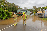 Pictured: Two firemen attend the flooded Dulais Fach Road (B4434) between the areas of Aberdulais and Tonna in Neath, south Wales, UK. Saturday 13 October 2018<br /> Re: Flooding caused by Storm Callum in the Neath area, south Wales, UK.