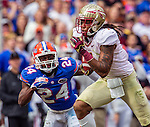 Gators defensive backs Brian Poole (24) tracks FSU wide receiver Kelvin Benjamin (1) after a reception and scored on a 47 yard touchdown reception in the first half of the #2 ranked Florida State Seminoles 37-7 win over the Florida Gators at Ben Hill Griffin Stadium in Gainesville, Florida November 30, 2013.