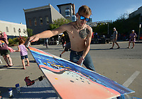 NWA Democrat-Gazette/ANDY SHUPE<br /> Artist Aon Alta of Lowell tilts a painting that he was creating Thursday, Sept. 6, 2018, for a crowd during First Thursday on the Fayetteville downtown square. Alta's &quot;psychedelic abstractinism&quot; painting began as a performance at a party.