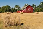 Red barn with hay rolls in western North Dakota