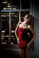 Blonde woman wearing red dress leaning against wall by window with lights of Manhattan behind her