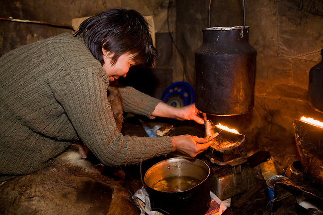 Natasha Nomro, a Chukchi woman, trims the wick of an oil lamp inside the Polog (inner tent) of her Yaranga. Chuktskiy Peninsula, Chukotka, Siberia, Russia.