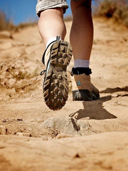 Woman's legs in hiking boots, hiking a dry rocky trail.