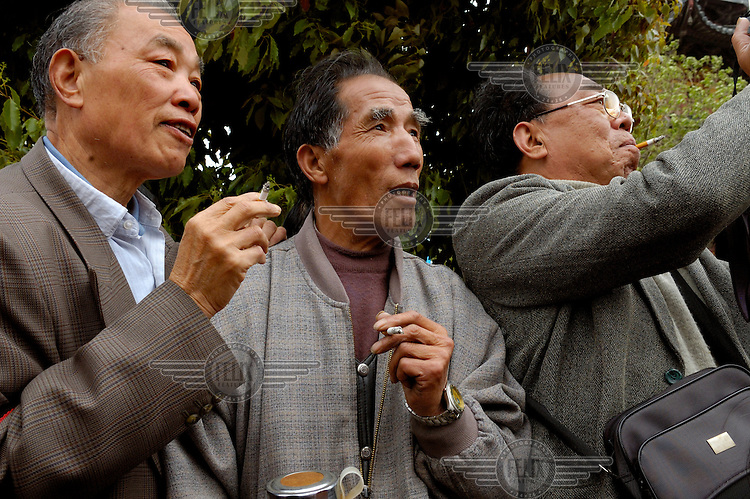Chinese tourists with cigarettes watching a performance at Longhua Temple Fair.